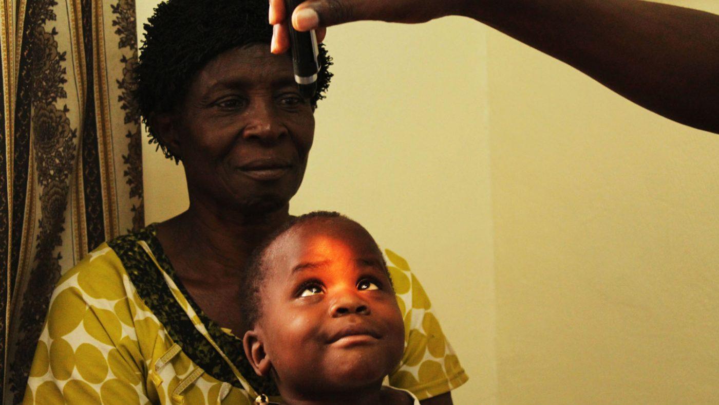 En synsspesialist lyser en lommelykt i Criscents øyne, mens Criscents bestemor holder ham på fanget.