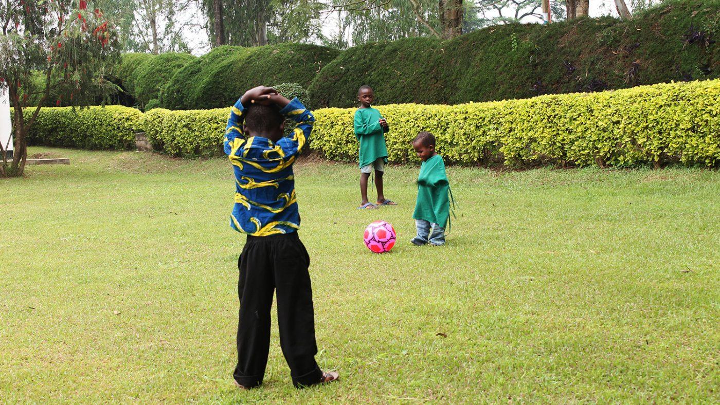 Criscent løper etter en rosa ball i en liten fotballkamp på gresset foran sykehuset.