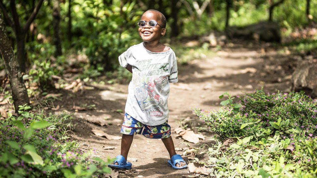 Criscent står i skogen i nærheten av hjemmet sitt og smiler bredt.