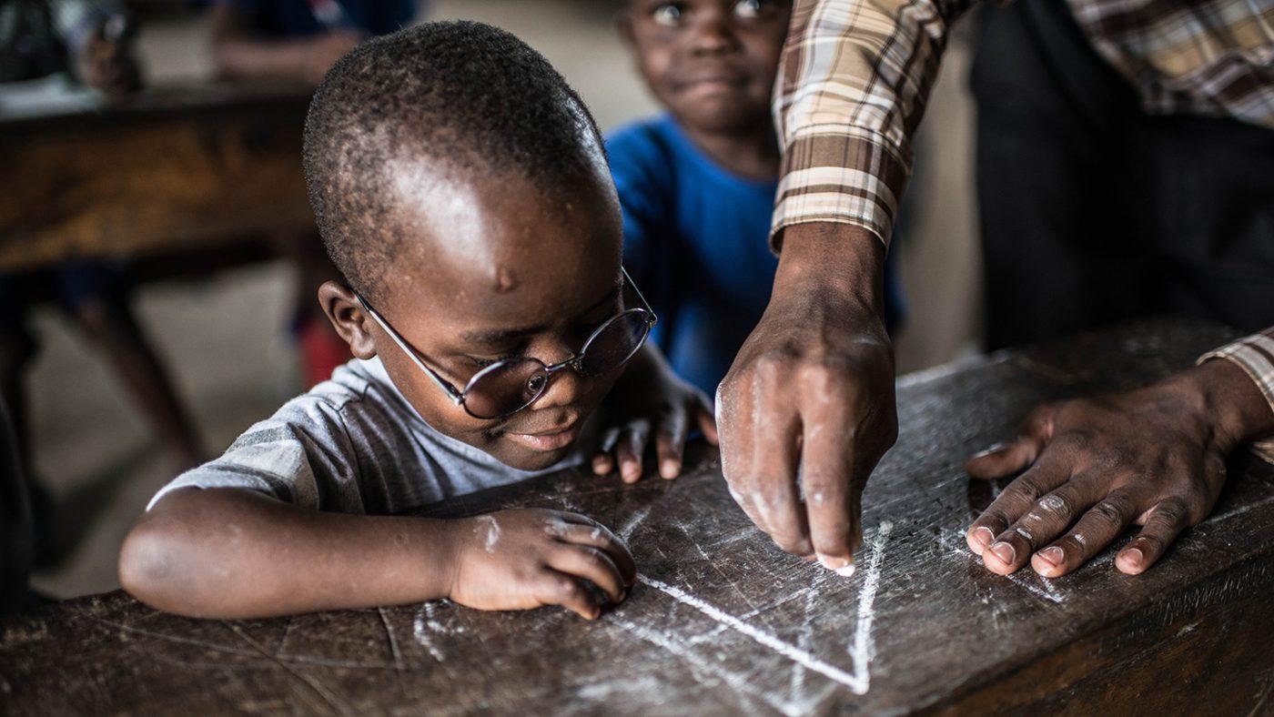 Criscent blir vist hvordan han skriver bokstaven A med kritt av læreren sin.