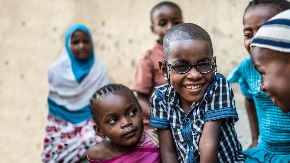 Saidi smiler bredt til kamera, i de splitter nye brillene sine.
