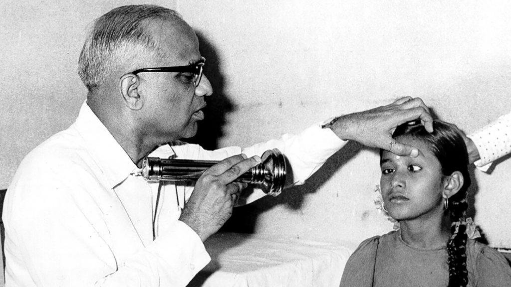 En lege undersøker øynene til en jente i India på 1950-tallet.