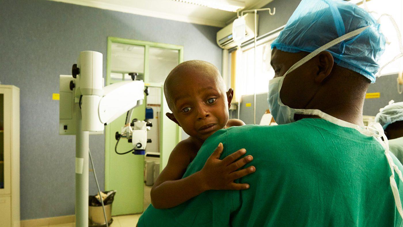 Baraka klamrer seg til en sykepleier i redsel før operasjonen.