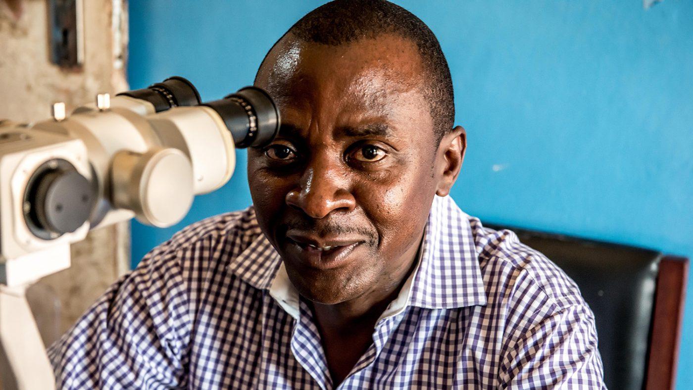 Dr Gerald Msukwa smiler mot kamera.