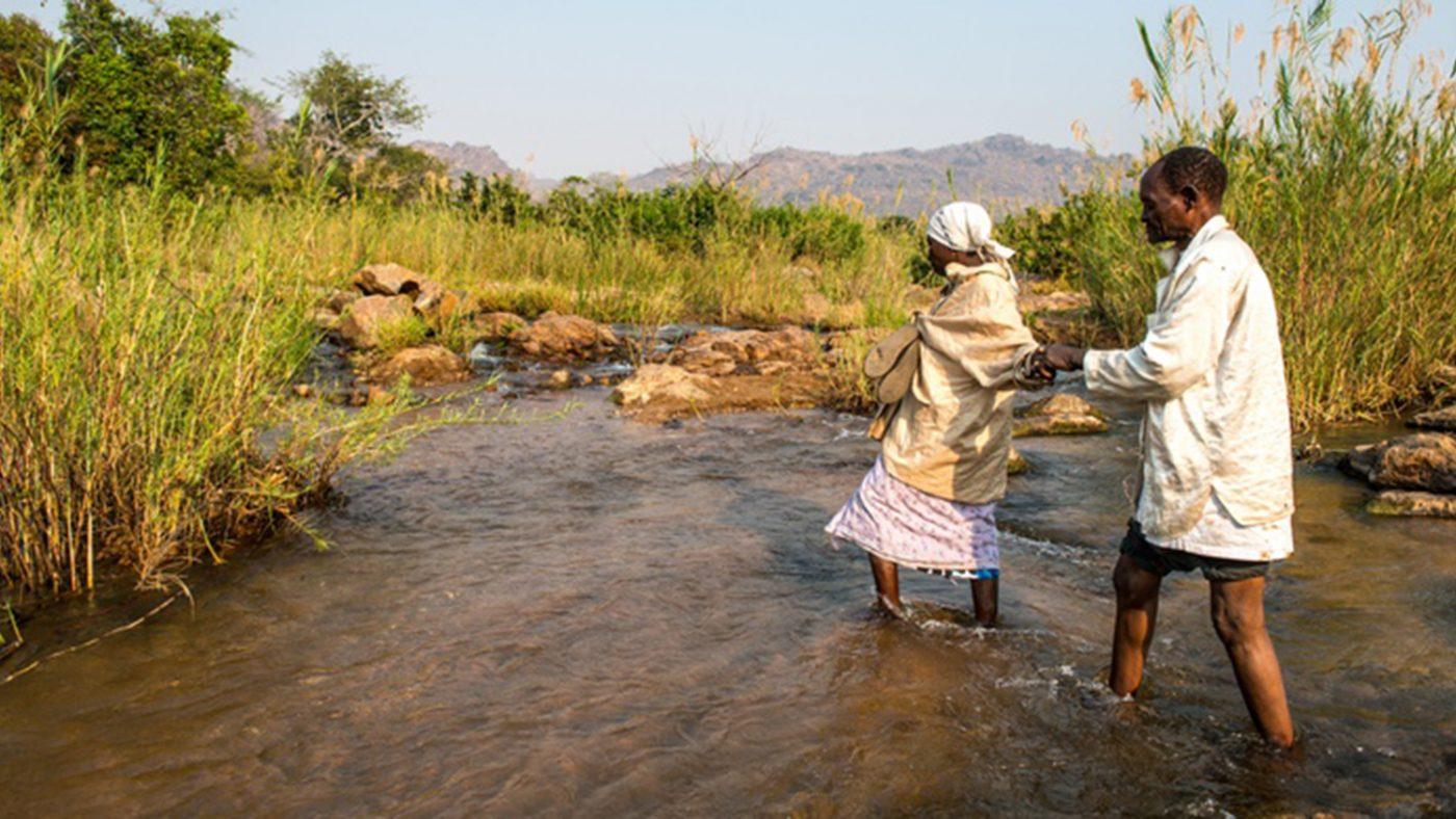En blind mann blir hjulpet av kona over en elv.