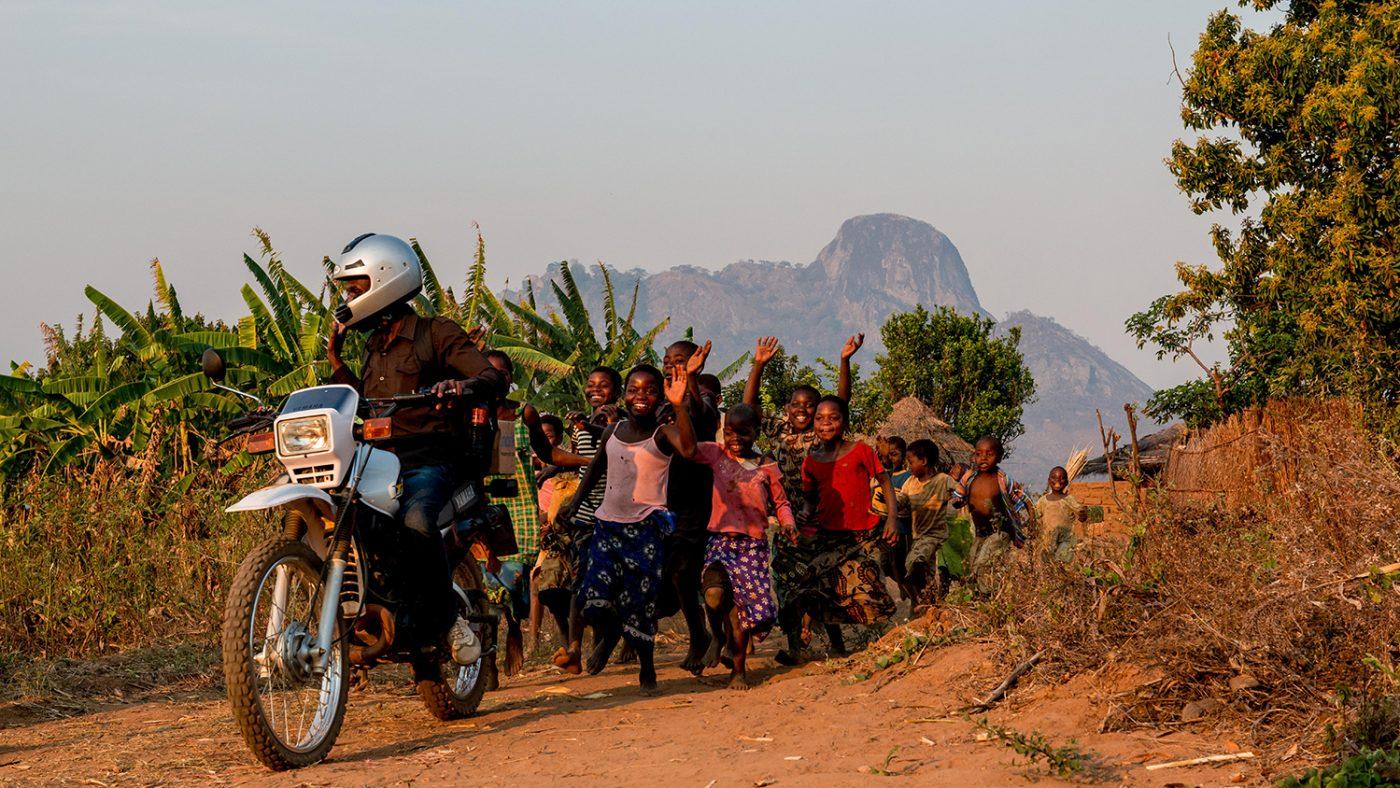 Madalitso Nyangulu kjører motorsykkelen sin med en flokk glade barn løpende bak.