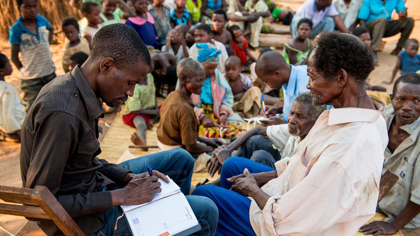 Madalitso Nyangulu sitter sammen med en mann og tar notater.