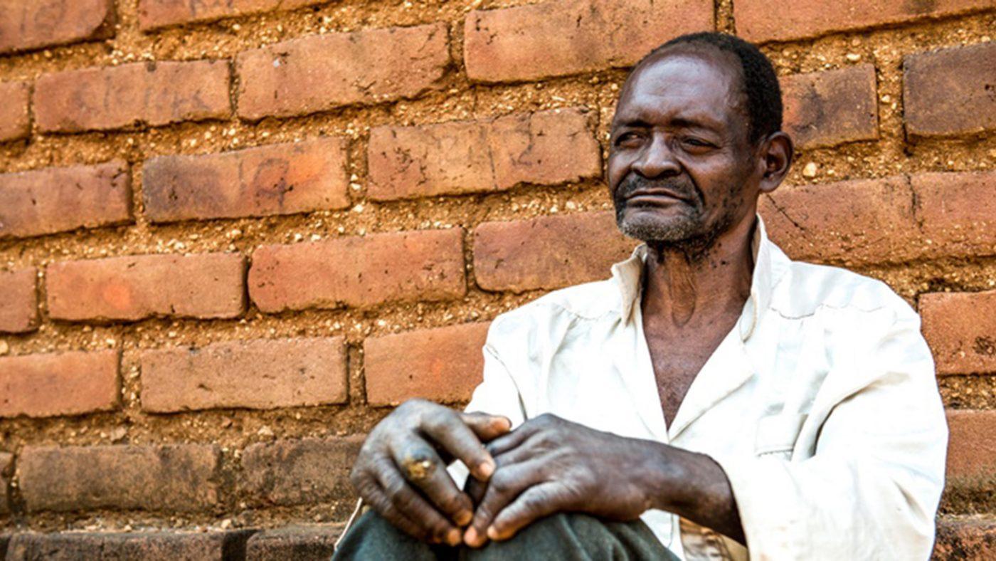 Mr Winesi, som har grå stær på begge øynene, sitter utenfor huset sitt i Mwanza-distriktet.