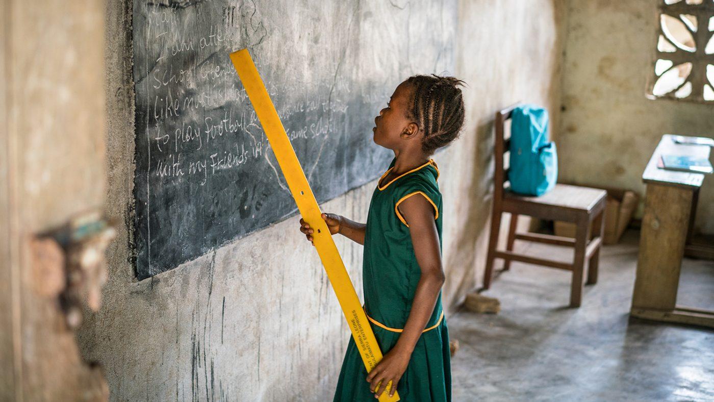 Aminata står ved tavla og holder en linjal for å peke ut ord.