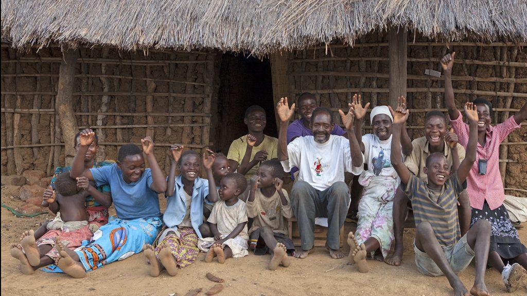 Winesi smiler sammen med familien utenfor huset deres i Malawi