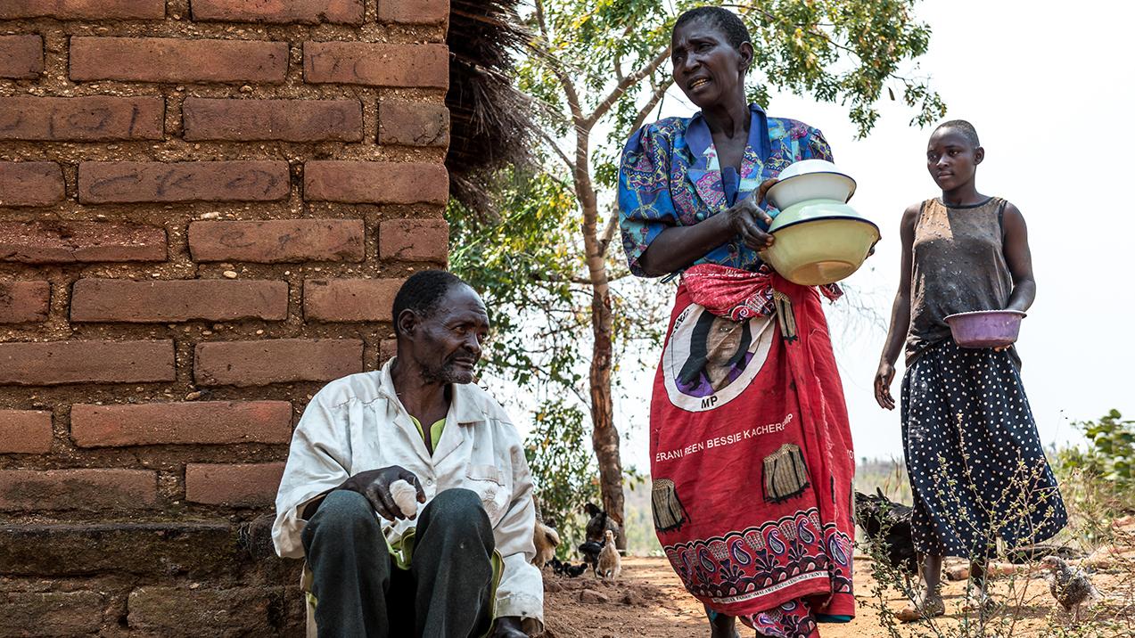 Winesi sitter på gulvet, før grå stær-operasjonen. Familien gjør husarbeid rundt ham.