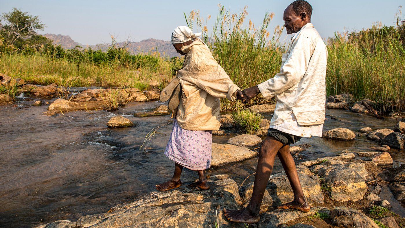 Winesi blir ledsaget over en elv av kona.