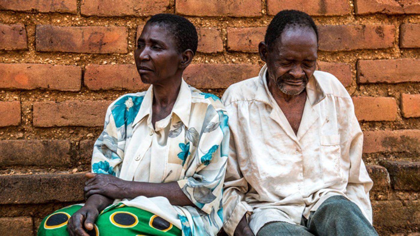 Winesi, som har grå stær, sitter utenfor huset sitt i Malawi sammen med kona Namaleta.