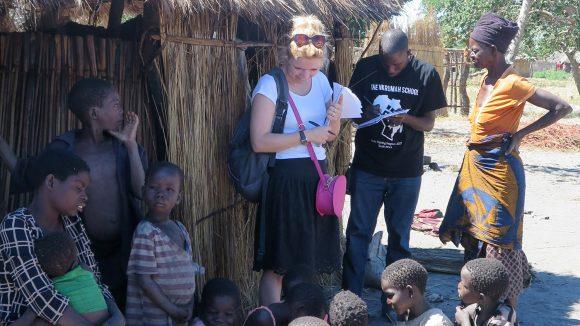 Sightsavers' Jo Howard sår i skyggen og snakker med landsbybeboere.