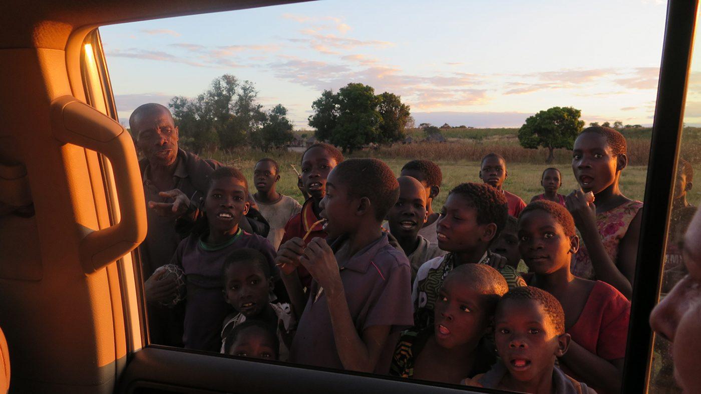 Mange barn fra landsbyen samler seg foran bilvinduet for å vinke farvel til Sightsavers' medarbeidere.