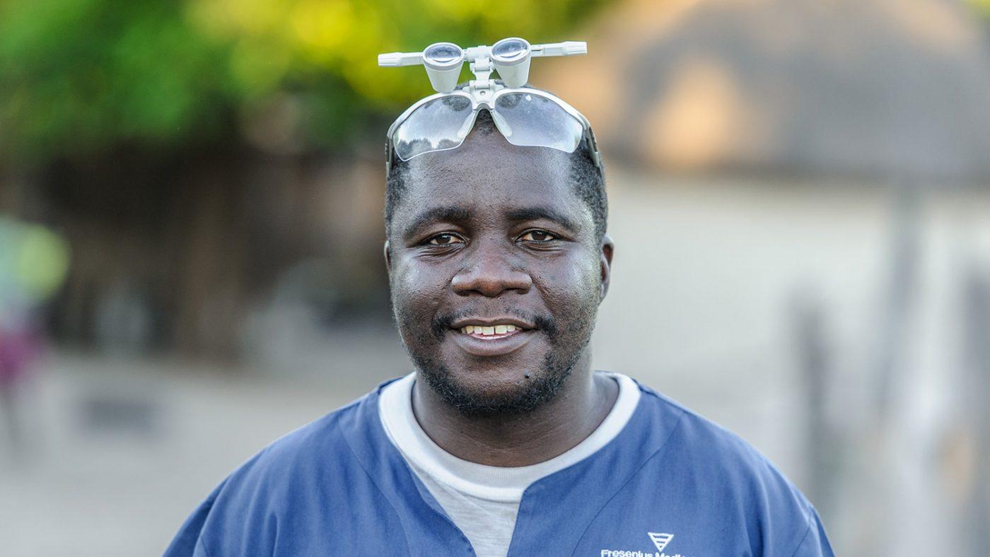 Mr Ndalela står med undersøkelsesbrillene sine på hodet og smiler mot kamera.
