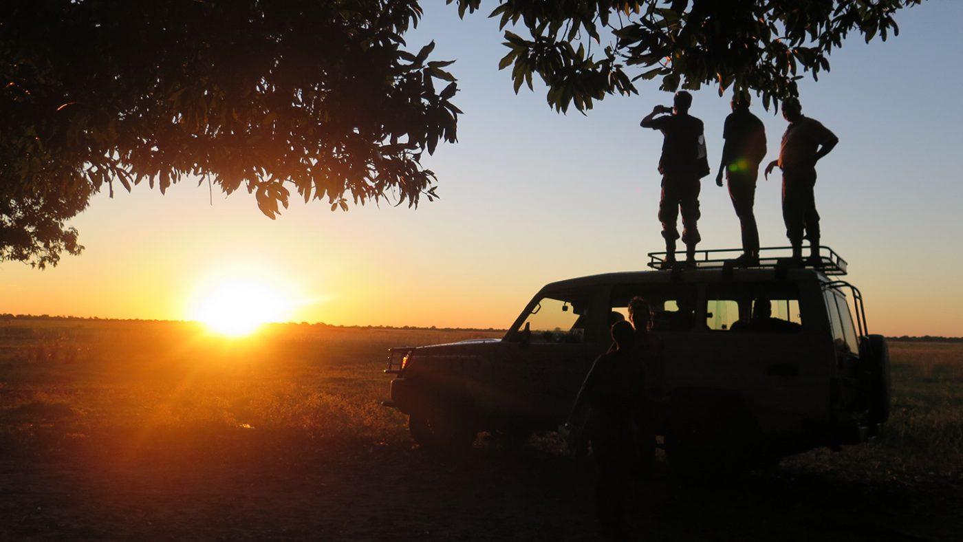Silhuetten av tre personer som står på taket til en firehjulsdrevet bil og nyter solnedgangen.