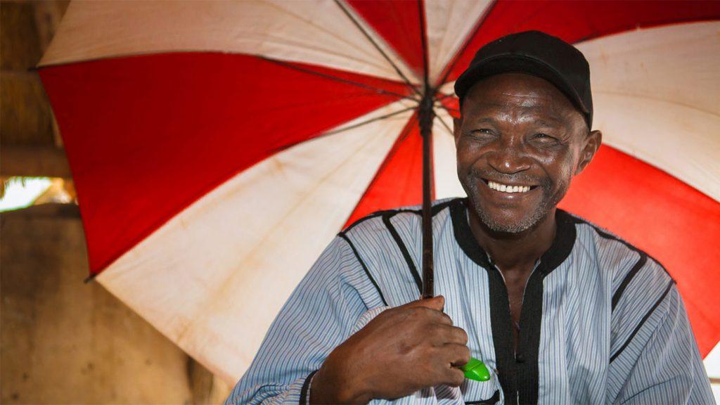 Mamadou Samine, en samfunnsdistributør frå Senegal holder en paraply og smiler mot camera.