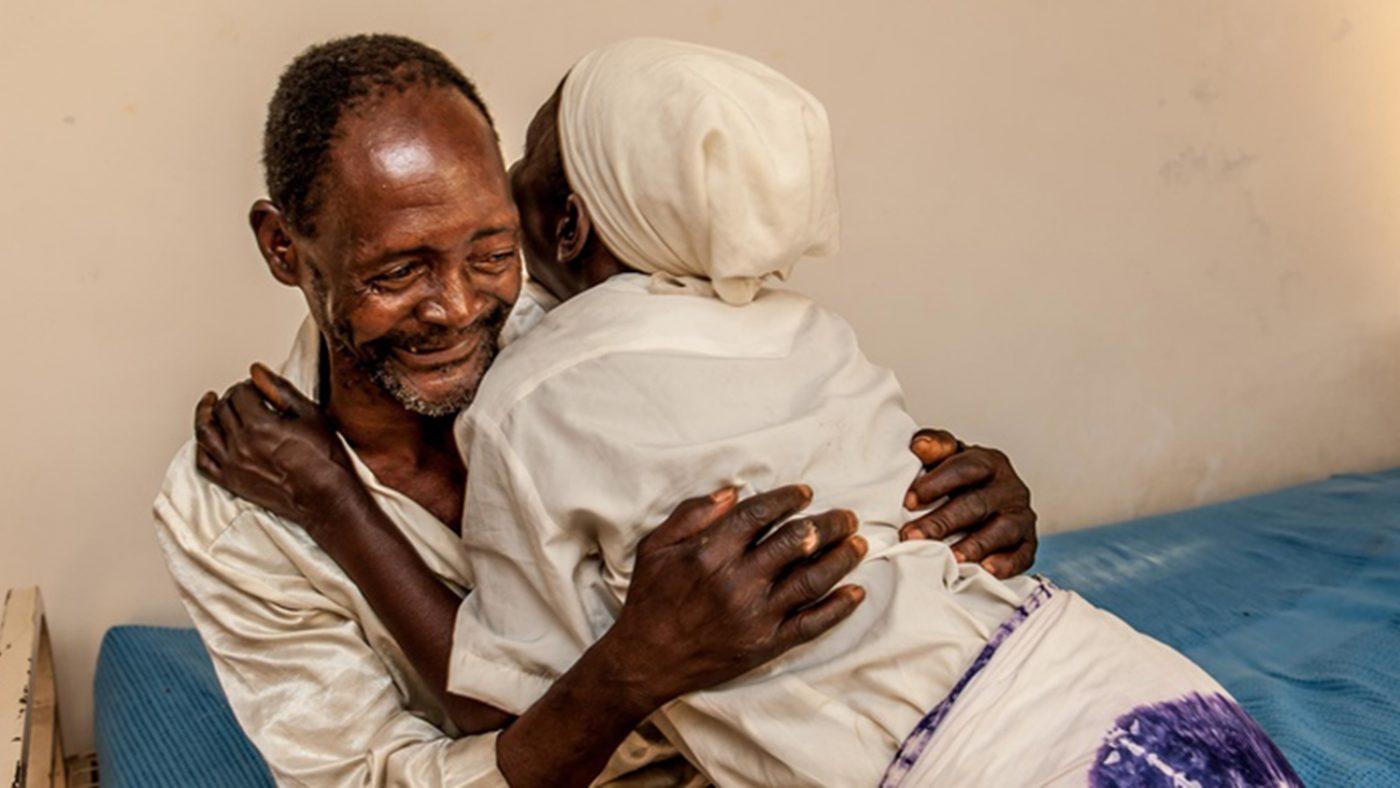 Winesi, en 69 år gammel mann, klemmer kona og smiler etter grå stær-operasjonen sin.