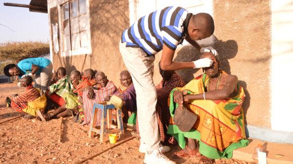 To helsearbeidere renser øynene til menn i tradisjonelle afrikanske klær.