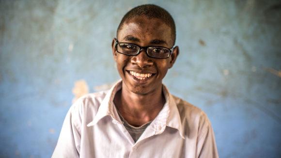 En gutt med briller smiler.