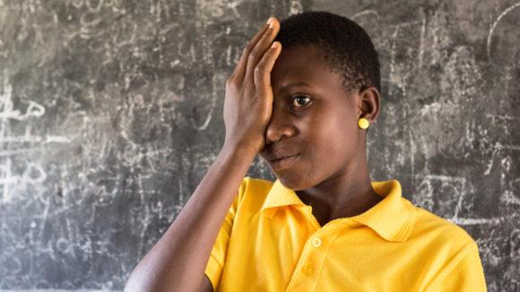 En jente dekker til øyet med en hånd under en synstest på en skole i Ghana.