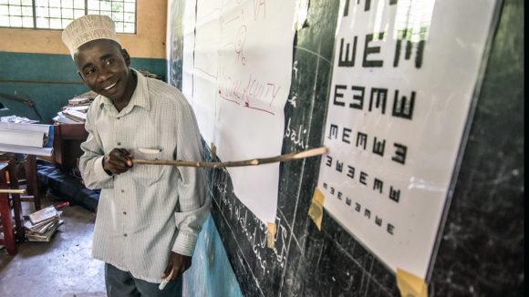En lærer på Zanzibar bruker en tavle med bokstaver for å teste barns syn.
