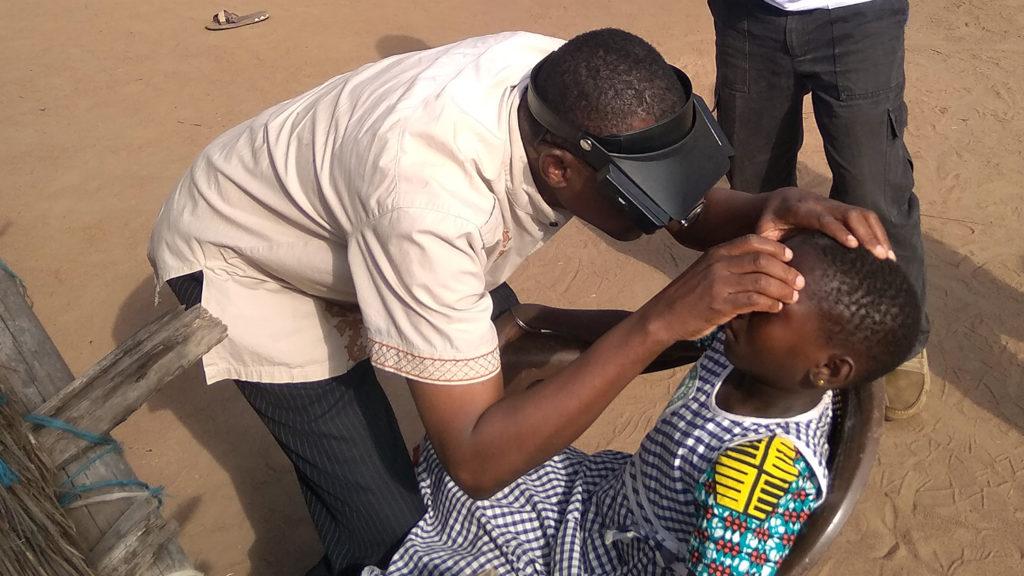 En frivillig i Elfenbenskysten lærer hvordan man kan oppdage trakom ved å undersøke øyne til et barn.