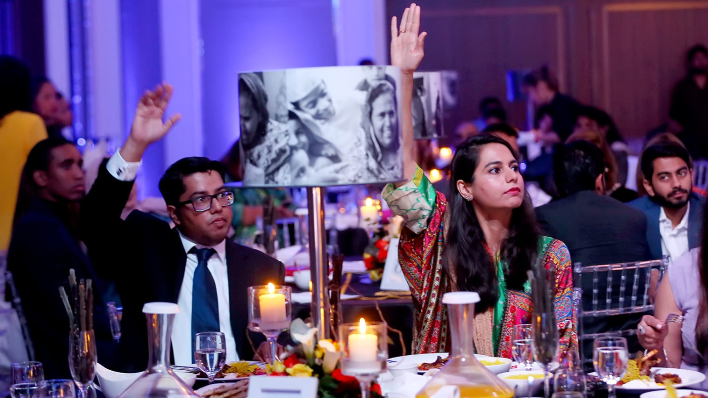A couple sitting at an extravagant dinner table raise their hands in the air to bid during the auction.