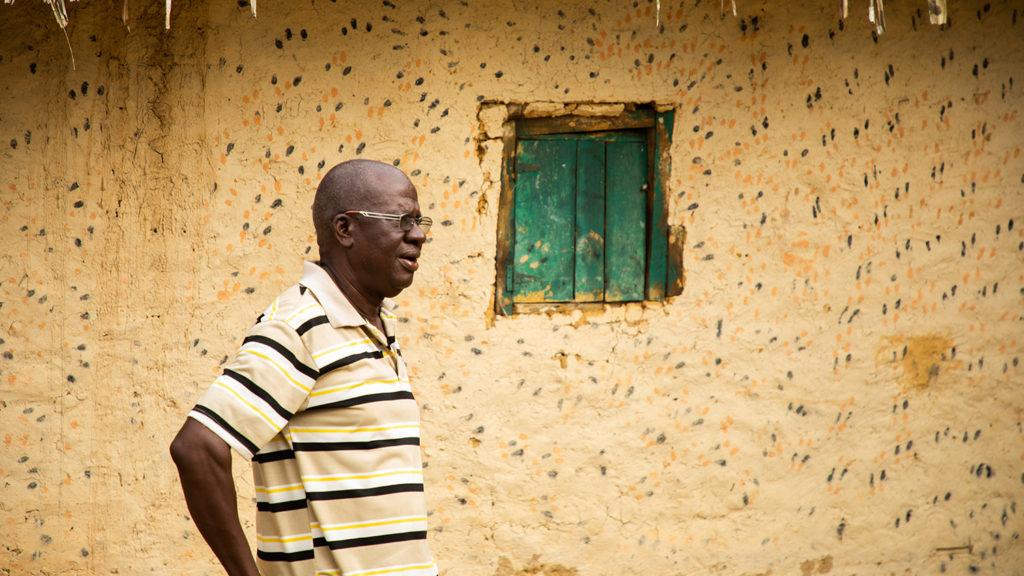 Lincoln Gankpala kledd i en stripete t-skjorte utenfor et hjem i Gorzohn, Liberia.