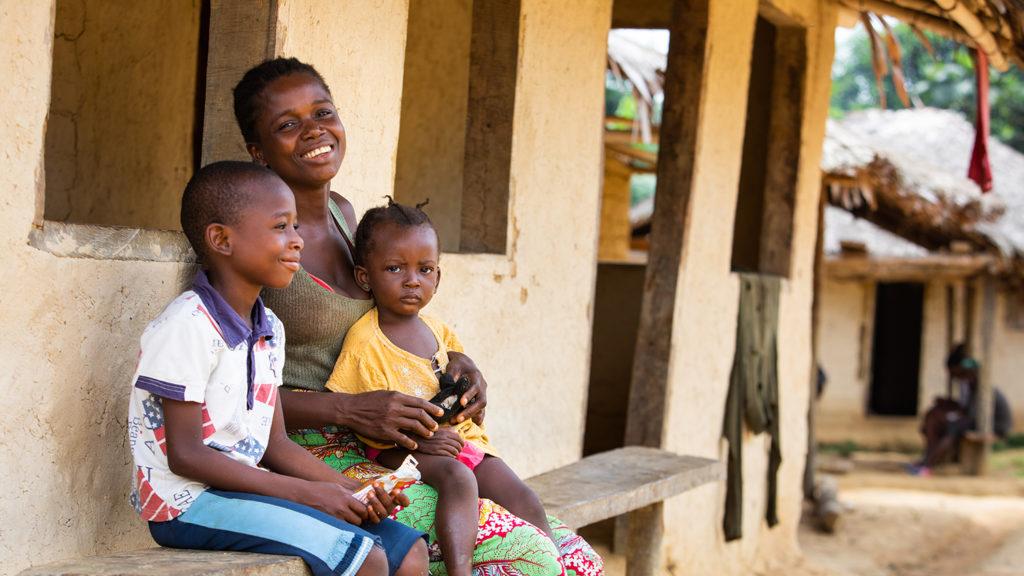 Sia Tamba sitter sammen med sønnen og datteren utenfor hjemmet deres.