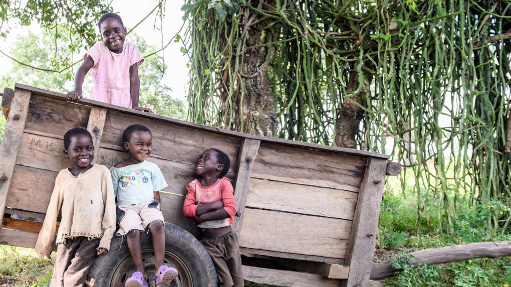 En gruppe barn smiler mens de er samlet rundt en trevogn.