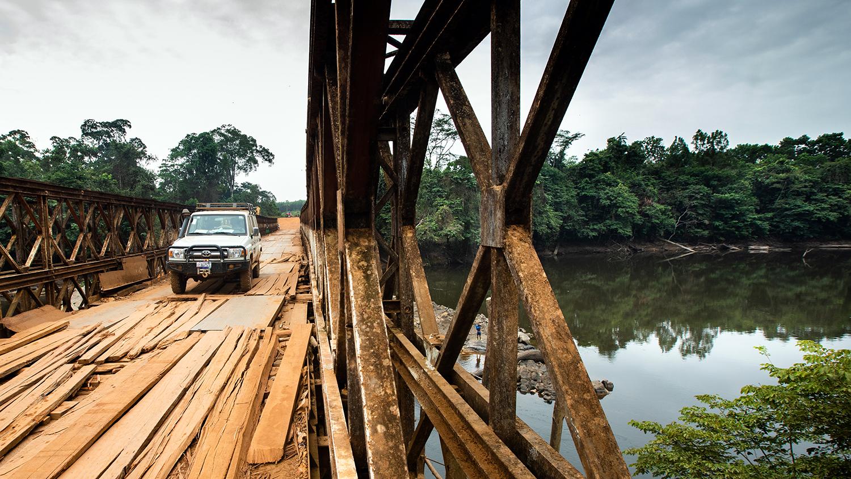 En Sightsavers 4x4 krysser en falleferdig bro over en elv i River Cess County i Liberia.