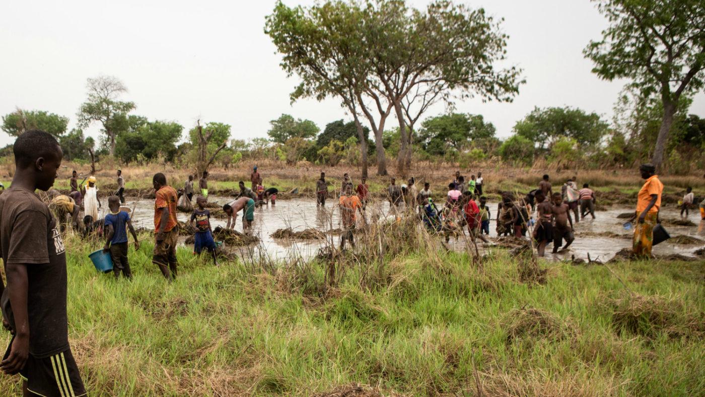 Mange mennesker står å fisker i Pru-elva i Ghana.