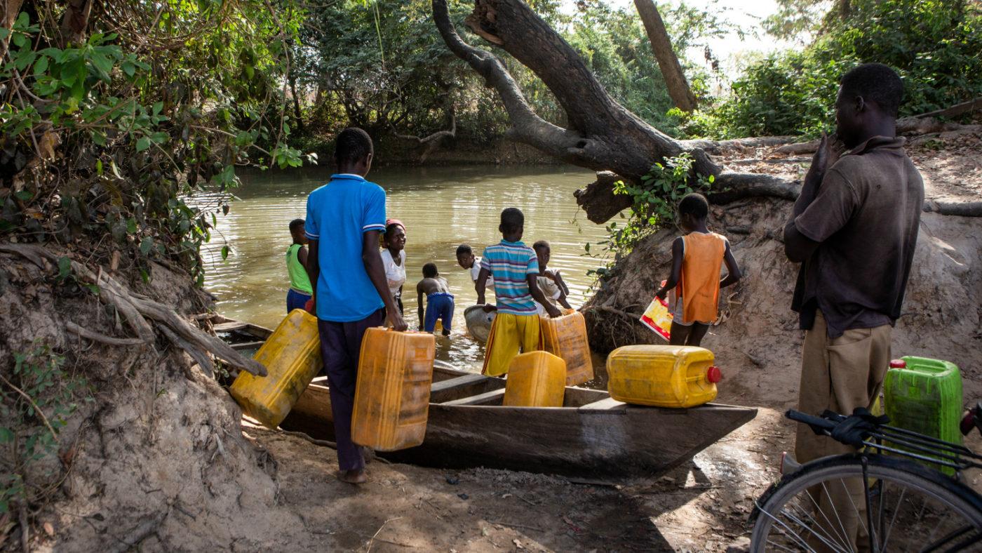 Flere menn bruker store gule beholdere for å hente vann fra Pru-elva.