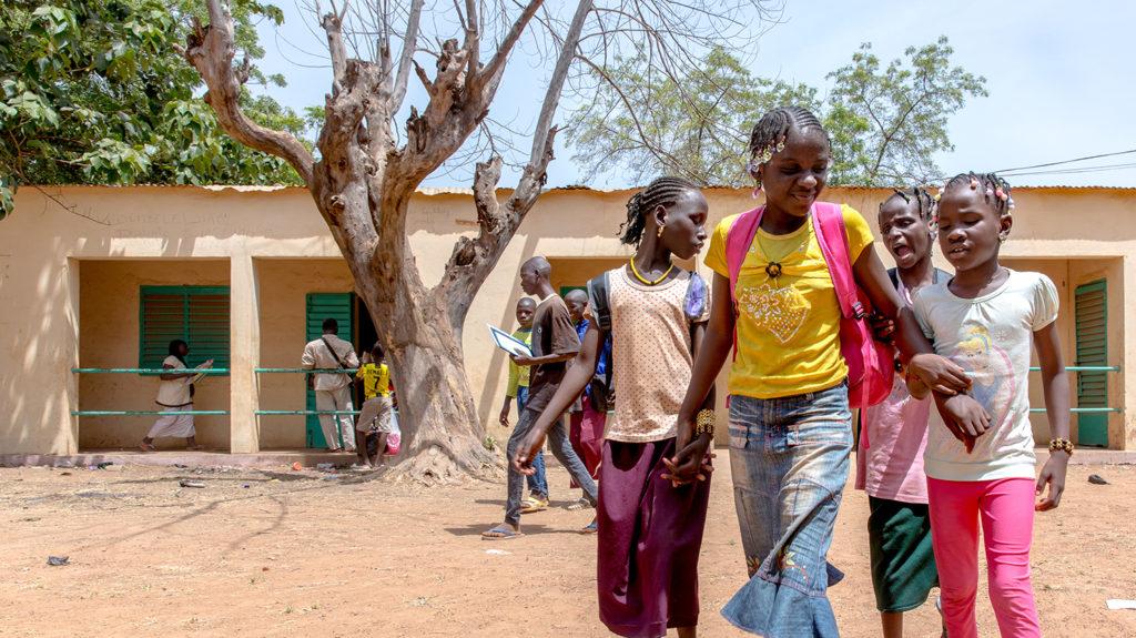En gruppe elever holder hverandre i armene utenfor skolen deres i Mali.