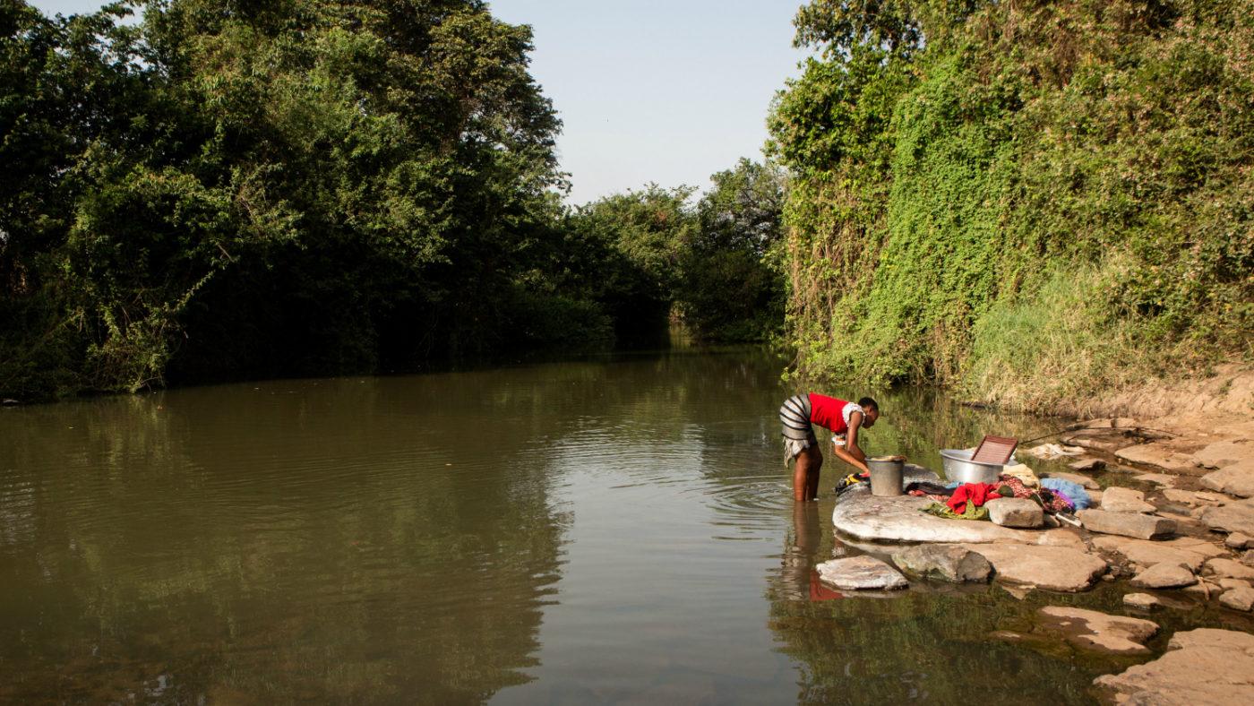 En kvinne vasker klærne sine i Pru-elva i Asubende, Ghana.