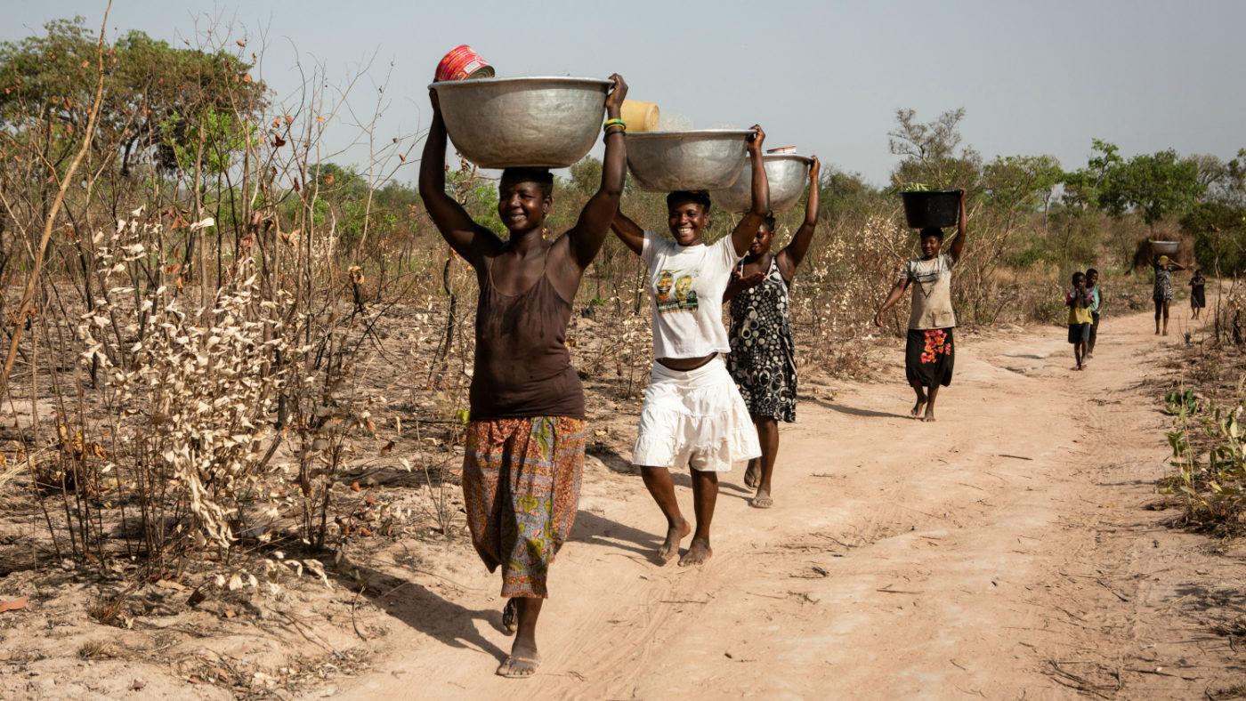 Fire kvinner går på en støvete vei med skåler på hodet for å hente vann.