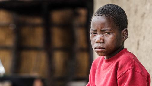 Mwiza sitter utenfor hjemmet sitt og ser trist ut.