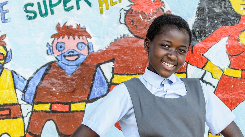 En elev smiler foran et veggmaleri i Zambia.