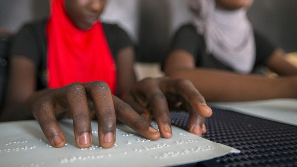 En elev fra Senegal leser blindeskrift i klasserommet.