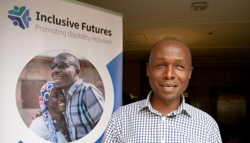 Deus Turyatemba stands next to an Inclusive Futures poster