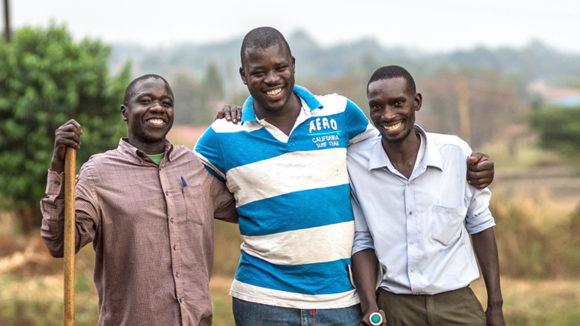 Tre menn står arm i arm og holder stokker.