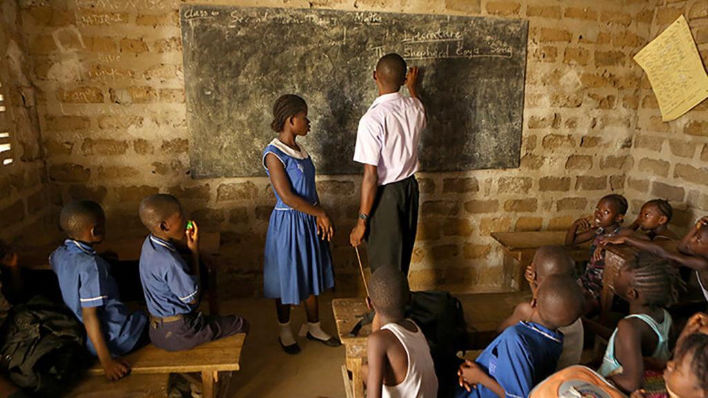 Et skarpt bilde av et klasserom i Sierra Leone. Læreren står foran tavla sammen med en elev mens de andre klassekameratene ser på.