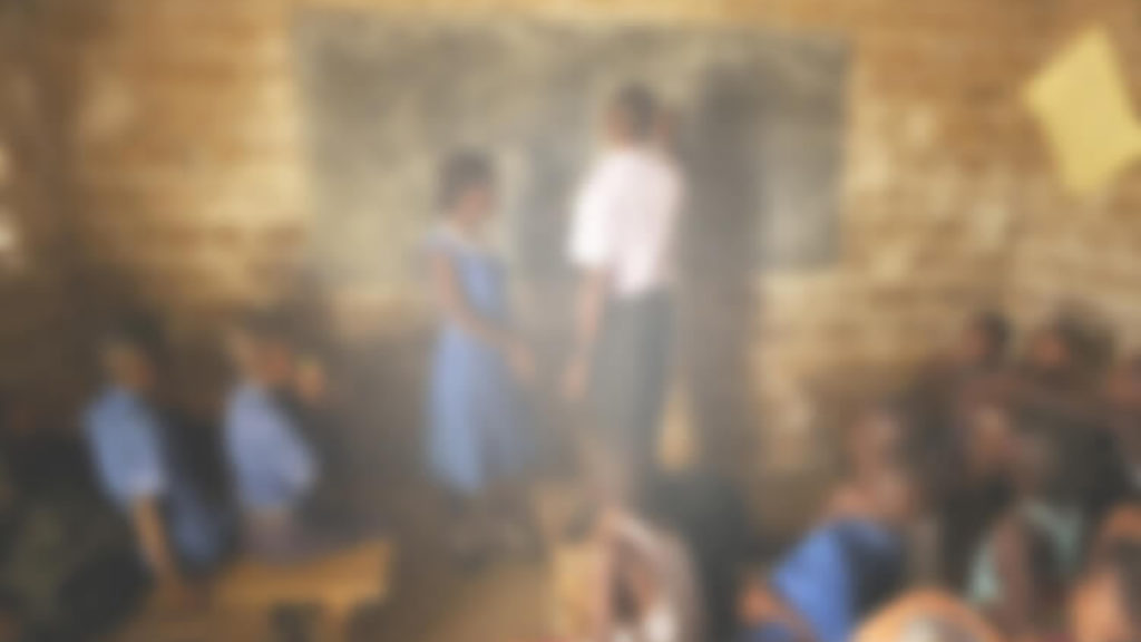 Et uklart bilde av et klasserom i Sierra Leone. Bildet er utydelig og uskarpt med et hvitaktig skjær. Det er vankelig å se læreren og tavla klart.