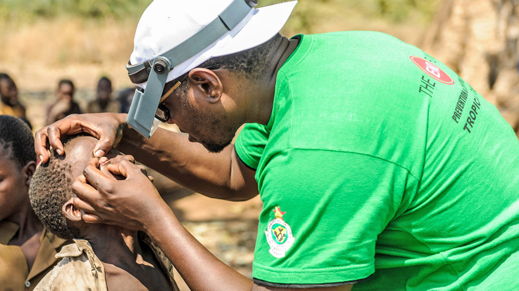 A child in Zimbabwe has his eyes checked by a health worker.