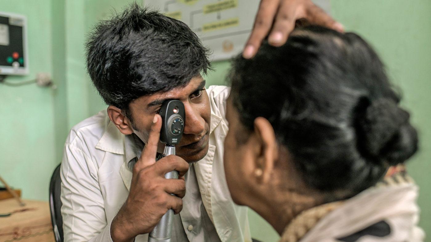 En helsearbeider undersøker øynene til en kvinne.