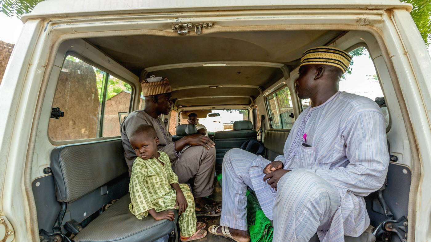 Muzi and his dad in a van ready to go to the hospital in Sokoto Nigeria