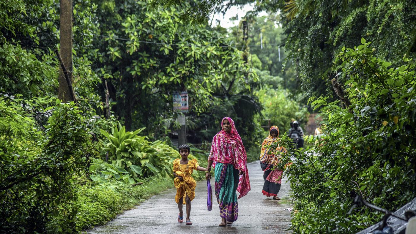 En kvinne og et barn går på en våt sti under et tre.