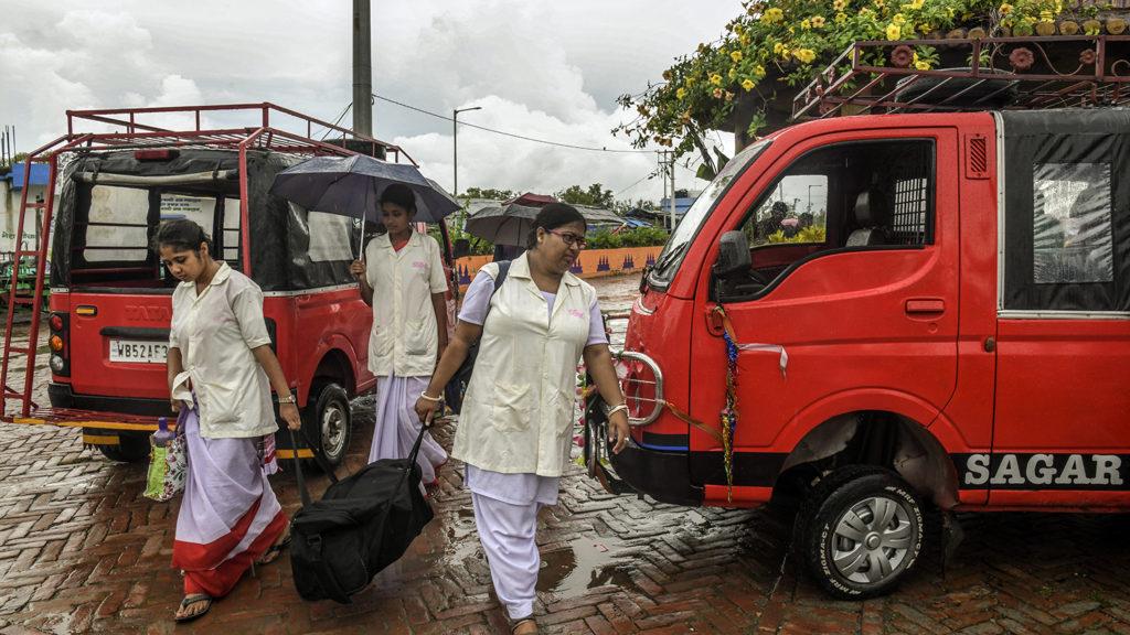 Kvinner går forbi to varebiler